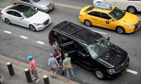 Traffic surrounds a ride-hailing taxi picking up passengers in New York