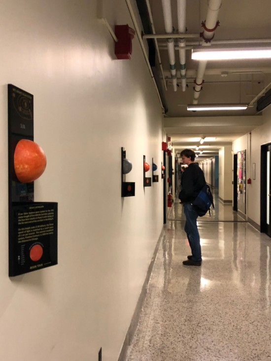 Student standing in hallway looking at model planets and informational plaques on wall