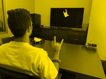 Image of person wearing wristband, making a hand gesture, and gesture appearing on a television screen