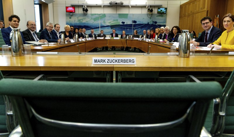 An empty chair with Mark Zuckerberg's name beside it, faced by lawmakers from multiple countries